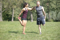 La femme faisant l'étirage s'exerce avec l'entraîneur personnel en parc Photos stock