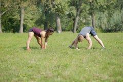 La femme faisant l'étirage s'exerce avec l'entraîneur personnel en parc Photo stock