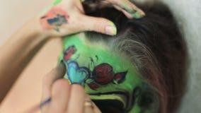 La femme faisant l'art de visage d'aquagrim sur le maquillage de Halloween avec ses glands de mains verdissent le squelette fasci banque de vidéos