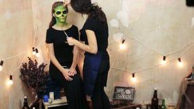La femme faisant l'art de visage d'aquagrim sur le maquillage de Halloween avec ses glands de mains verdissent le squelette fasci clips vidéos