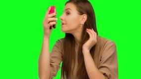 La femme faisant le maquillage, regardant le téléphone aiment dans un miroir banque de vidéos
