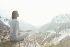 La femme faisant le yoga s'exerce au-dessus du dessus d'une montagne image stock