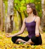 La femme faisant le yoga s'exerce en stationnement d'automne Image stock