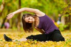 La femme faisant le yoga s'exerce en stationnement d'automne Photographie stock libre de droits