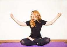 La femme faisant le yoga s'exerce et les pilates pose sur le tapis sur le fond blanc Asana Le concept des sports, de la forme phy Images stock