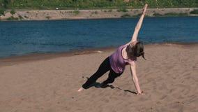 La femme faisant les exercices folâtre sur les banques de la rivière dans la ville Exercices pour des mains dans la planche clips vidéos