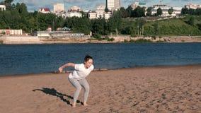 La femme faisant les exercices folâtre sur les banques de la rivière dans la ville Sauter de la position assise banque de vidéos