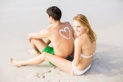 La femme faisant un symbole de coeur équipe dessus de retour tout en appliquant une lotion de protection solaire Photos stock