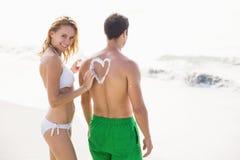 La femme faisant un symbole de coeur équipe dessus de retour tout en appliquant une lotion de protection solaire Images libres de droits