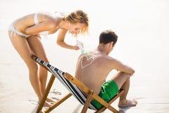 La femme faisant un symbole de coeur équipe dessus de retour tout en appliquant une lotion de protection solaire Photographie stock