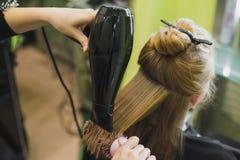 La femme fait des cheveux coupés dans le salon images stock