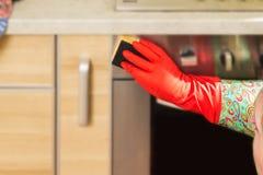 La femme fait des corvées dans la cuisine à la maison Images stock