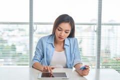 La femme fait des emplettes en ligne avec le PC de comprim? images libres de droits