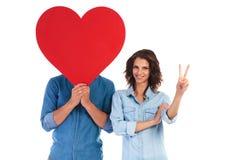 La femme fait le signe de victoire près de l'homme avec le coeur au-dessus du visage Photographie stock