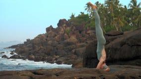 La femme fait le support principal sur la pierre plate près du mouvement lent d'océan banque de vidéos