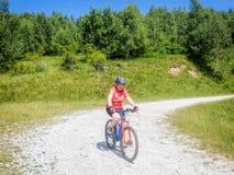 La femme fait un cycle en parc national Retezat photos libres de droits