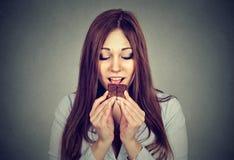 La femme a fatigué des restrictions de régime implorant la barre de chocolat Image stock