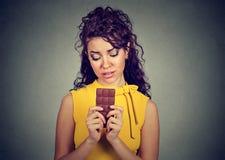 La femme a fatigué des restrictions de régime implorant la barre de chocolat de bonbons Image libre de droits