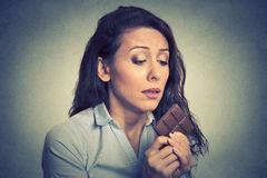 La femme a fatigué des restrictions de régime implorant le chocolat de bonbons Images libres de droits
