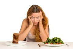 La femme a fatigué des restrictions de régime implorant un biscuit photos stock