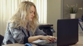La femme fatiguée d'affaires dans le costume travaille à l'ordinateur dans le bureau images stock