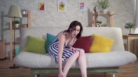 La femme fatiguée s'asseyant sur le divan enlève ses talons et fait le massage de pied clips vidéos