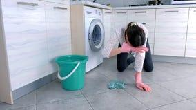 La femme fatigu?e dans les gants en caoutchouc roses lave le plancher de cuisine avec un tissu Tuiles grises sur le plancher banque de vidéos