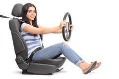 La femme feignant pour conduire a assis sur un siège de voiture Photographie stock libre de droits