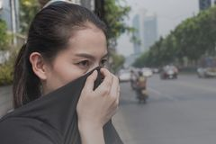La femme ferme son nez avec la main en raison de la mauvaise pollution du trafic photo stock