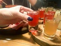 La femme, fille tient dans sa main avec une manucure sur ses doigts un verre rouge délicieux, un tir avec de l'alcool fort, vodka image stock