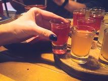 La femme, fille tient dans sa main avec une manucure sur ses doigts un verre rouge délicieux, un tir avec de l'alcool fort, vodka images stock