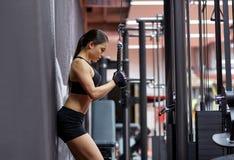 La femme fléchissant le bras muscles sur la machine de câble dans le gymnase image stock