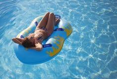 la femme flotte sur un matelas gonflable Photos libres de droits