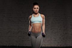 La femme féminine de forme physique avec le corps musculaire, font sa séance d'entraînement avec des haltères Images stock