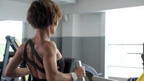 La femme folâtre fait des exercices pour des muscles d'épine sur le simulateur de bloc banque de vidéos