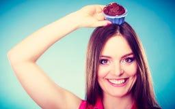 La femme folle tient le gâteau de chocolat sur la tête Photo stock