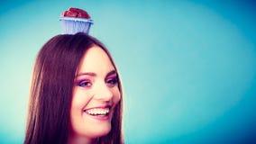 La femme folle tient le gâteau de chocolat sur la tête Photos stock