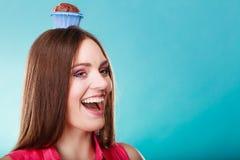 La femme folle tient le gâteau de chocolat sur la tête Photo libre de droits