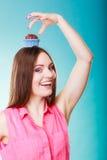 La femme folle tient le gâteau de chocolat sur la tête Image libre de droits