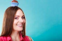 La femme folle tient le gâteau de chocolat sur la tête Photographie stock libre de droits