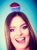 La femme folle tient le gâteau de chocolat sur la tête Image stock