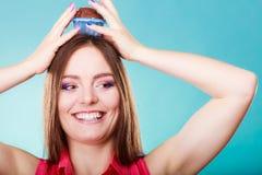La femme folle tient le gâteau de chocolat sur la tête Images stock