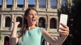 La femme font le selfie au téléphone portable près de Colosseum à Rome, Italie Adolescente souriant dans le mouvement lent banque de vidéos