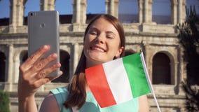 La femme font le selfie sur le mobile près de Colosseum à Rome, Italie Drapeau italien de vague d'adolescent dans le mouvement le banque de vidéos