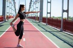 La femme forte de forme physique s'étirant au pont piétonnier avant établissent L'espace vide photos stock