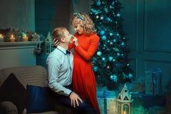 La femme frotte l'homme de flirt de nez pendant la nuit de Noël Image stock
