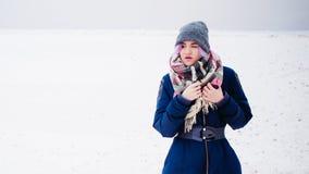la femme fume une cigarette électronique dans la rue près de la rivière couverte de neige Images stock
