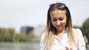 La femme gaie écrit un message sur le téléphone et les promenades dans le parc d'été clips vidéos