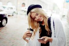 La femme gaie dans le café potable de matin de rue et utilisent son smartphone Photo libre de droits