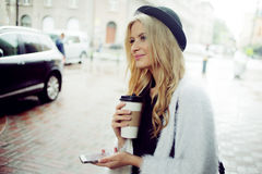 La femme gaie dans le café potable de matin de rue et utilisent son smartphone Images stock